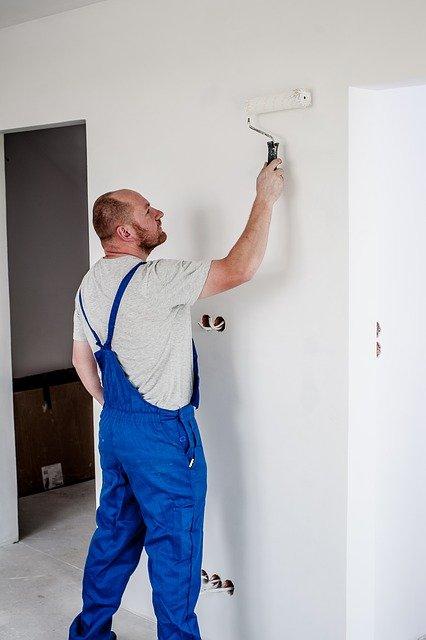 En maler, der ruller en mur